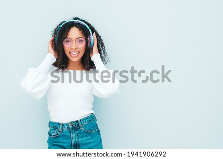 Beautiful black woman with afro curls hairstyle.Smiling model in sweater and jeans.Sexy carefree female listening music in wireless headphones.Posing in studio near light blue wall