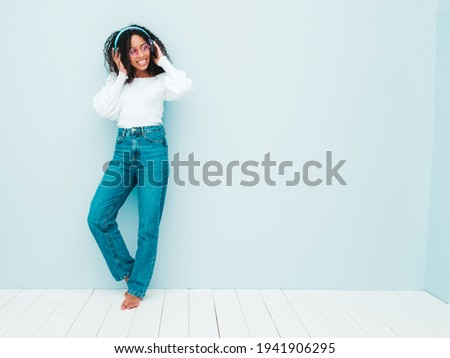 Beautiful black woman with afro curls hairstyle.Smiling model in sweater and jeans.Sexy carefree female listening music in wireless headphones.Posing in studio near light blue wall.Full length