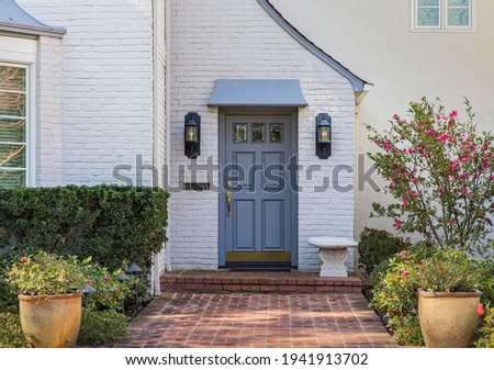 Blue front door of traditional style home with brick entry and white brick exterior. Royalty-Free Stock Photo #1941913702