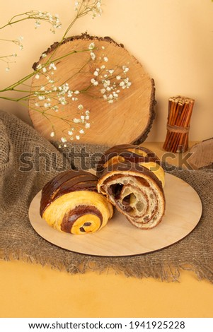 Delicious fresh puff pastry buns with chocolate on wooden background  Royalty-Free Stock Photo #1941925228