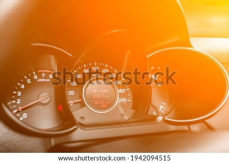 speedometer of a modern car with an integrated fuel gauge in the tank with white arrows under the yellow and orange neon color Royalty-Free Stock Photo #1942094515