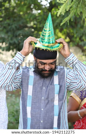 A middle-aged Indian man with a turban on his head trying to wear a paper hat for a birthday