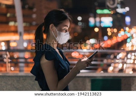 Side-view of beautiful young Asian happy woman wearing covid-19 face mask standing over footbridge checking smartphone and browsing through apps while checking email Royalty-Free Stock Photo #1942113823