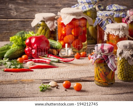 Preserved and fresh vegetables on wooden background #194212745