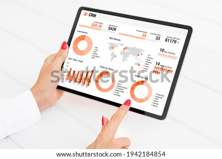 Charts and infographics on the screen of tablet computer showing different business sales and performance data