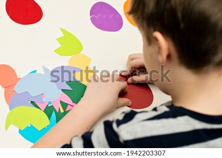 Different color paper eggs on white table. Easter theme game, find other side of figure.