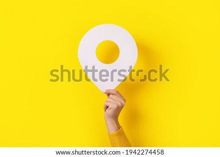 3d white pin in hand over yellow background Royalty-Free Stock Photo #1942274458