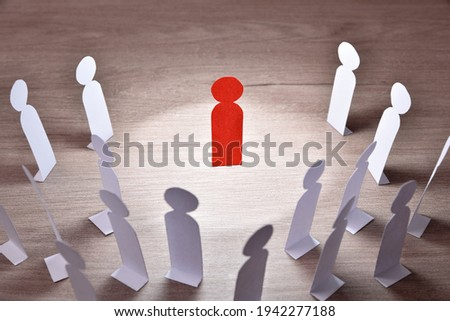 Representation of person preaching in front of a group of people by means of paper cutouts in the shape of a person on wooden table elevated view Royalty-Free Stock Photo #1942277188