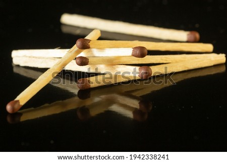 Wooden matches with brown with sulfur heads on black background Royalty-Free Stock Photo #1942338241