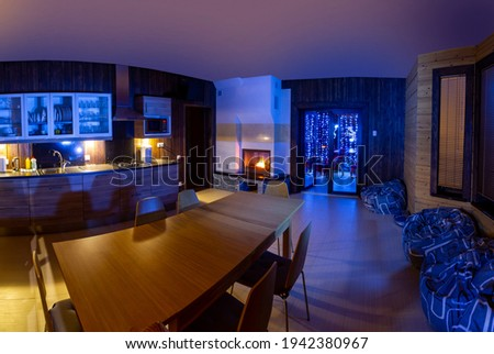 home interior kitchen. Large wooden table is located in kitchen. Evening interior with neon lighting. Dining room with fireplace. Rest room is combined with kitchen. Fireplace in lounge. Royalty-Free Stock Photo #1942380967