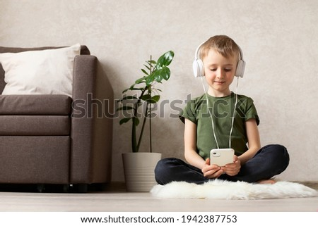 A child boy with a phone sits on a sheep skin rug with headphones watching cartoons, listening to music, playing games, talking on the phone.
