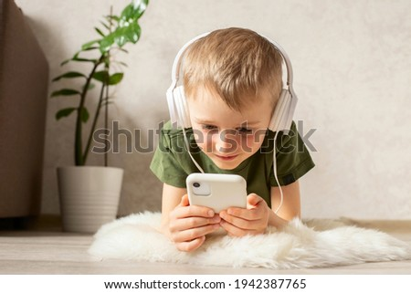 A child boy with a phone is lying on the floor with headphones watching cartoons, listening to music, playing games, talking on the phone.