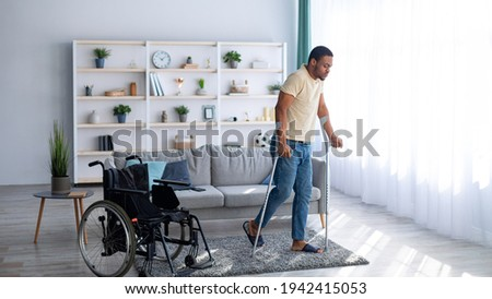 Rehabilitation concept. Young black guy walking with crutches after using wheelchair at home, panorama Royalty-Free Stock Photo #1942415053