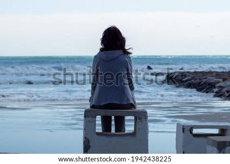 Girl alone looking at the sea Royalty-Free Stock Photo #1942438225