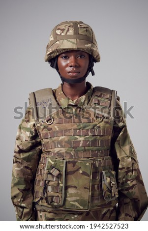 Studio Portrait Of Serious Young Female Soldier In Military Uniform Against Plain Background Royalty-Free Stock Photo #1942527523
