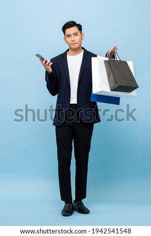 Young handsome southeast Asian man holding mobile phone and shopping bags in light blue studio isolated background Royalty-Free Stock Photo #1942541548