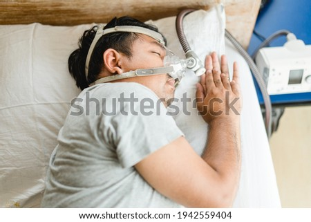 Asian fat man wearing Cpap mask sleeping in bed, snoring man.Obstructive sleep apnea therapy. Cpap therapy, medical health, Sleep test, Good sleep, Machine, Patient, Sleep Disordered Breathing.Sdb  Royalty-Free Stock Photo #1942559404