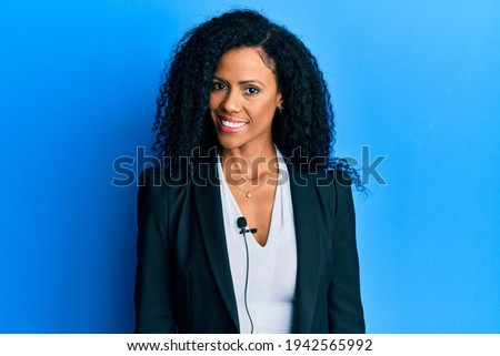 Middle age african american woman using lavalier microphone looking positive and happy standing and smiling with a confident smile showing teeth