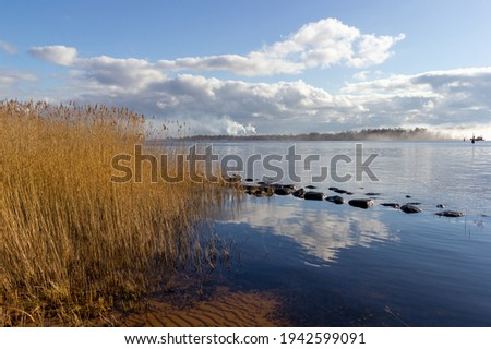 River bank with a row of boulders on a sunny spring day. Blue sky with white cumulus clouds reflected in the water. Last year's dry reeds on the shore. Latvia Royalty-Free Stock Photo #1942599091