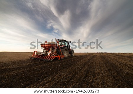 Farmer with tractor seeding - sowing crops at agricultural field. Plants, wheat. Royalty-Free Stock Photo #1942603273