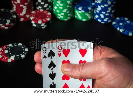 Poker cards with one pair combination. Close up of a gambler hand is holding playing cards in casino Royalty-Free Stock Photo #1942624537