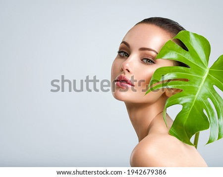 Young beautiful woman with green leave near face and body. Skin care beauty treatments concept.  Closeup girl's face with green leave. White model with clean, health skin of face - posing at studio Royalty-Free Stock Photo #1942679386