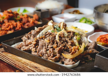 Beef bulgogi close up Korean BBQ dinner on a wooden table with other foods blurred in the background. Royalty-Free Stock Photo #1942763686