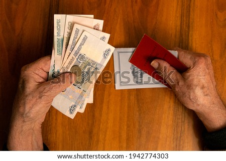 Elderly man holding russian ruble banknotes in one hand and pension certificate with passbook in another. The concept of pension, payment and money savings. Royalty-Free Stock Photo #1942774303