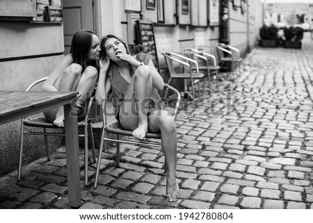Two girls friends sitting at the table of outdoors cafe and whispering. Black and white photo.