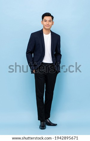 Full length portrait of happy smiling young handsome southeast Asian businessman standing on light blue studio background Royalty-Free Stock Photo #1942895671