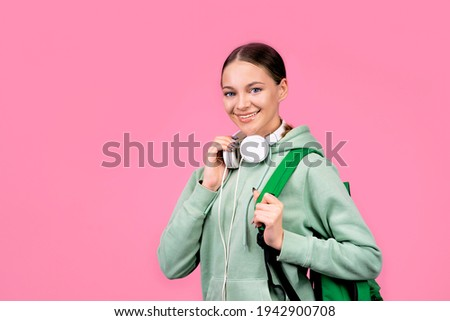 Happy smiling woman, student girl goes to study with a backpack and with headphones. Portrait on a solid monochrome pink background.