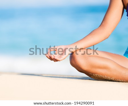 Happy relaxed young woman practicing yoga outdoors at the beach. Lotus position, Cloe up detail photo of hand. #194290091