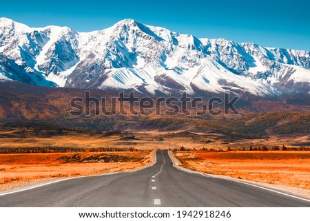 Beautiful road in autumn mountains. Chuysky tract and view of North-Chuya mountain ridge in Altai, Siberia, Russia. Snow-covered mountain peaks and yellow autumn forest Royalty-Free Stock Photo #1942918246