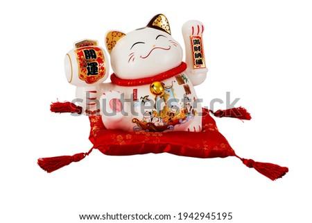 Maneki Neko cat.Japanese lucky cat,Maneki Neko isolated on red mat. Chinese lucky cat.The hieroglyphs on the cats translates as: Good luck, Full of wealth.
