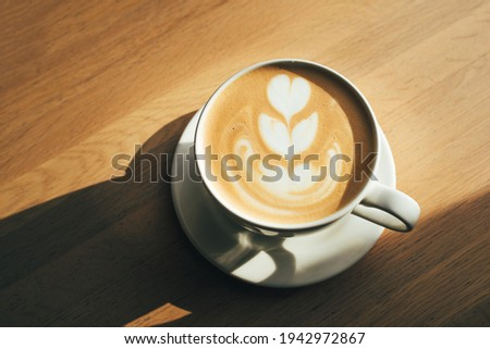 Cup of cappuccino on wooden table on a sunny morning.