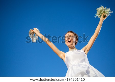 Young happy bride jumping over blue sky. focus on face #194301410
