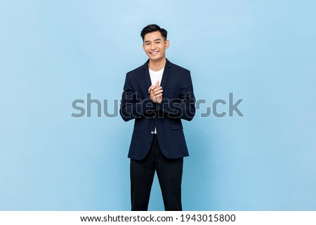 Smiling young handsome southeast Asian man clapping hands impressively in light blue studio isolated background Royalty-Free Stock Photo #1943015800