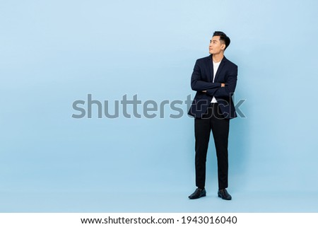 Full length portrait of young handsome southeast Asian businessman with arms crossed looking up sideway to copy space on light blue studio background Royalty-Free Stock Photo #1943016040