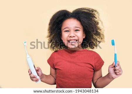 Smiling African American little girl holds manual and electric sonic toothbrushes, isolated on beige background