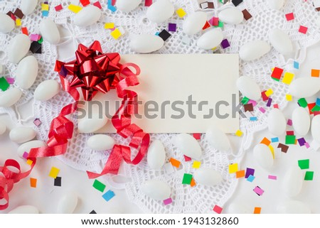 Traditional Almond Candies on handmade lace cloth with blank card and colorful paper decorations.Conceptual image of The Sugar Feast.