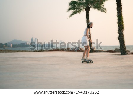 Asian Beautiful women surf skate or skateboard outdoors on beautiful summer day. Happy young women play surf skate at park near the beach on morning time. Sport activity lifestyle concept.