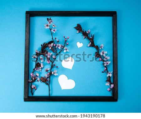 Creative spring composition made of cherry blossom tree branches and wooden picture frame on blue background with heart shape, spring concept, picture in picture, flat lay, top view