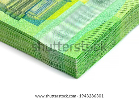 Macro shot of the European Union 100 EURO banknote, stack of banknotes lying on top of each other, close-up on a watermark, isolated on a white background.