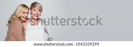 joyful young woman leaning on shoulder of stylish mother isolated on grey, banner Royalty-Free Stock Photo #1943339299