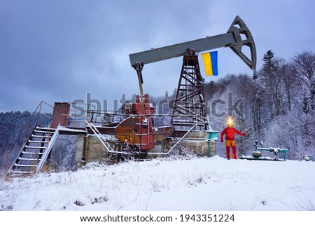 A working engineer at an oil and gas development of an old field checks the operation of mechanisms and control systems in the mountains after a winter in early spring. Flag of Ukraine yellow-blue. Royalty-Free Stock Photo #1943351224