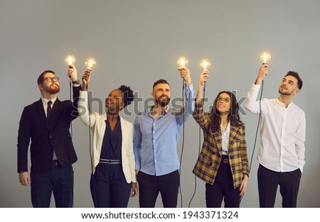 Group of happy creative young diverse business professionals holding glowing light bulbs standing on gray studio background. Innovative thinking, finding solution, people developing own idea concept Royalty-Free Stock Photo #1943371324