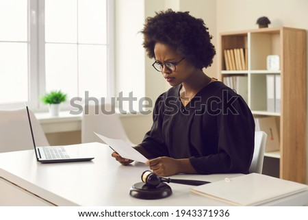 Frowning young african american female judge reading paper document sitting at desk front of laptop in courtroom. Legal trial or tribunal, paperwork and criminal data or jury order investigation Royalty-Free Stock Photo #1943371936