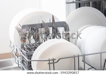 Dishes and cutlery on dishwashing machine. Clean dishes Royalty-Free Stock Photo #1943390857