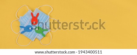 Easter bunny and medical masks lie on the left on a yellow background with space for the text to the right, top view close-up.