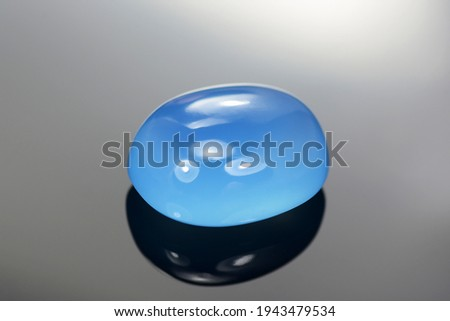 Natural blue chalcedony irregular oval cabochon polished gemstone. Heated, color enhanced, increased saturation. Closeup photo. Microcrystalline, cryptocrystalline varietie of quartz. Waxy luster.
